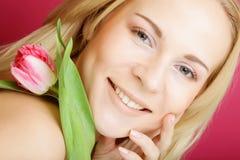 Blonde Frau mit rosa Tulpe Lizenzfreie Stockfotografie