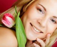 Blonde Frau mit rosa Tulpe Stockbild
