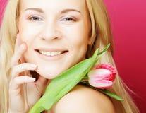 Blonde Frau mit rosa Tulpe Stockfotografie