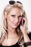 Blonde Frau mit rosafarbener Verfassung sprechend am Telefon Stockbild