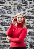 Blonde Frau mit roten Ohrenschützern lächelnd nahe einer Steinwand Stockfotografie