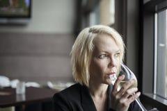 Blonde Frau mit schönem blaue Augen-Trinkglas weißen Wi Stockfotos