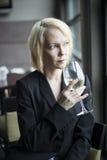 Blonde Frau mit schönem blaue Augen-Trinkglas weißen Wi Stockbilder