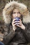 Blonde Frau mit schönen blauen Augen Kaffee trinkend Stockbild