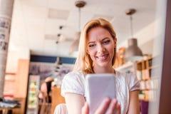 Blonde Frau mit Smartphone in der modernen Stadtcaféfunktion Lizenzfreies Stockbild