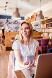 Blonde Frau mit Smartphone im Café, das an Notizbuch arbeitet Lizenzfreie Stockfotografie