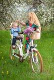 Blonde Frau mit Stadtfahrrad mit Baby im Fahrradstuhl Stockbild
