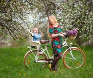 Blonde Frau mit Stadtfahrrad mit Baby im Fahrradstuhl Stockfoto