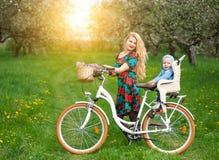 Blonde Frau mit Stadtfahrrad mit Baby im Fahrradstuhl Stockfotografie