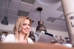 Blonde Frau mit Tablette im Café, lesend Stockfotografie