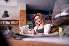 Blonde Frau mit Tablette in trinkendem Kaffee des Cafés Stockfotos