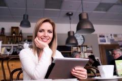 Blonde Frau mit Tablette in trinkendem Kaffee des Cafés Stockbild
