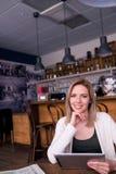 Blonde Frau mit Tablette in trinkendem Kaffee des Cafés Stockbilder