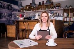 Blonde Frau mit Tablette in trinkendem Kaffee des Cafés Lizenzfreie Stockbilder