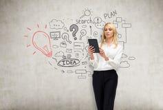 Blonde Frau mit Tabletten- und Startideenskizze auf Betonmauer Lizenzfreies Stockfoto