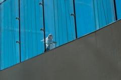 Blonde Frau mit Taschen im Sonnenschein auf Oslo-Opernhaus Lizenzfreies Stockfoto