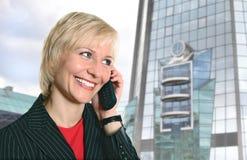 Blonde Frau mit Telefon nahe modernem Glasgebäude Stockbild