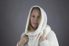 Blonde Frau mit weißer Strickjacke Stockfoto