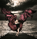 Blonde Frau mit wellenartig bewegender Seide in stürmischem Meer Lizenzfreie Stockfotos