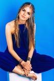 Blonde Frau mit Zöpfen im blauen Gesamten Stockbild
