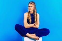 Blonde Frau mit Zöpfen im blauen Gesamtsitzen auf Stuhl Lizenzfreies Stockbild
