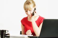 Blonde Frau mit Zeitschrift auf Mobiltelefon Stockfotografie