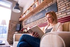 Blonde Frau mit Zeitung in trinkendem Kaffee des Cafés Stockfoto