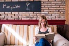 Blonde Frau mit Zeitung in trinkendem Kaffee des Cafés Stockfotografie