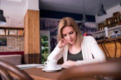 Blonde Frau mit Zeitung in trinkendem Kaffee des Cafés Stockbilder