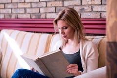 Blonde Frau mit Zeitung in trinkendem Kaffee des Cafés Stockbild