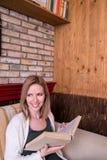 Blonde Frau mit Zeitung in trinkendem Kaffee des Cafés Lizenzfreies Stockbild
