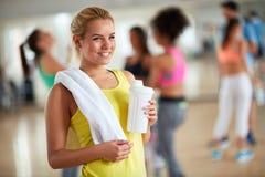 Blonde Frau nach der Ausbildung mit Tuch und Flasche Protein beve Lizenzfreies Stockfoto
