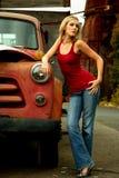 Blonde Frau nahe bei altem LKW Stockfoto