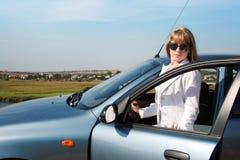 Blonde Frau nahe blauem Auto Lizenzfreies Stockbild