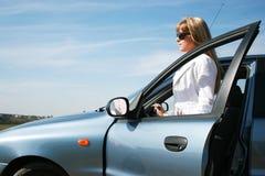 Blonde Frau nahe blauem Auto Lizenzfreie Stockbilder