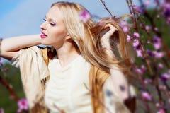 Blonde Frau nahe dem Pfirsichbaum Stockfotos
