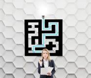 Blonde Frau nahe einer Labyrinthskizze Stockbild