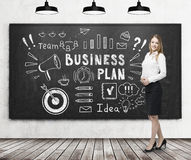 Blonde Frau nahe Unternehmensplan auf Tafel Lizenzfreies Stockbild