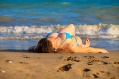Blonde Frau nimmt das Ein Sonnenbad nehmen auf dem Strandsand Stockbild