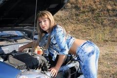 Blonde Frau repariert Automotor Lizenzfreie Stockbilder