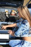 Blonde Frau repariert Automotor Lizenzfreie Stockfotografie