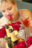 Blonde Frau riecht Rosen am Spiegel nahe Champagne Lizenzfreie Stockfotos