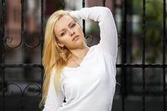 Blonde Frau am Roheisenzaun Stockbild