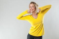 blonde Frau 20s mit gelbem Hemd lächelnd für Wohl Lizenzfreie Stockbilder