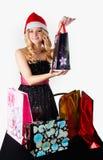 Blonde Frau in Sankt-Hut mit Einkaufstaschen Stockfotos