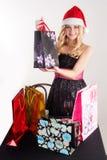 Blonde Frau in Sankt-Hut mit Einkaufstaschen Stockbild