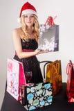 Blonde Frau in Sankt-Hut mit Einkaufstaschen Stockbilder