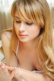 Blonde Frau schaut im Bett zur Hand Stockfotos