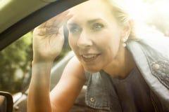 Blonde Frau schaut innerhalb eines Autos Lizenzfreie Stockfotos