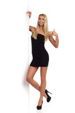 Blonde Frau in schwarzem Mini Dress Pointing Banner Lizenzfreie Stockbilder